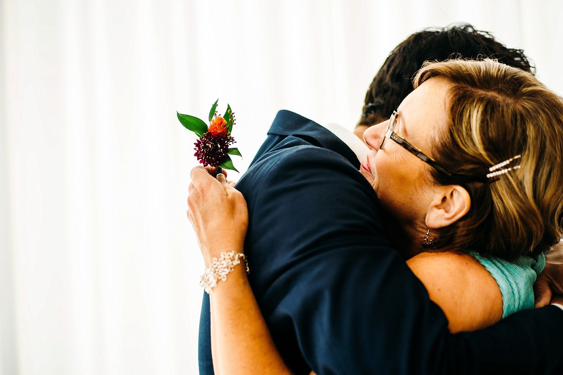 groom hugs mother during greenhouse loft wedding Chicago