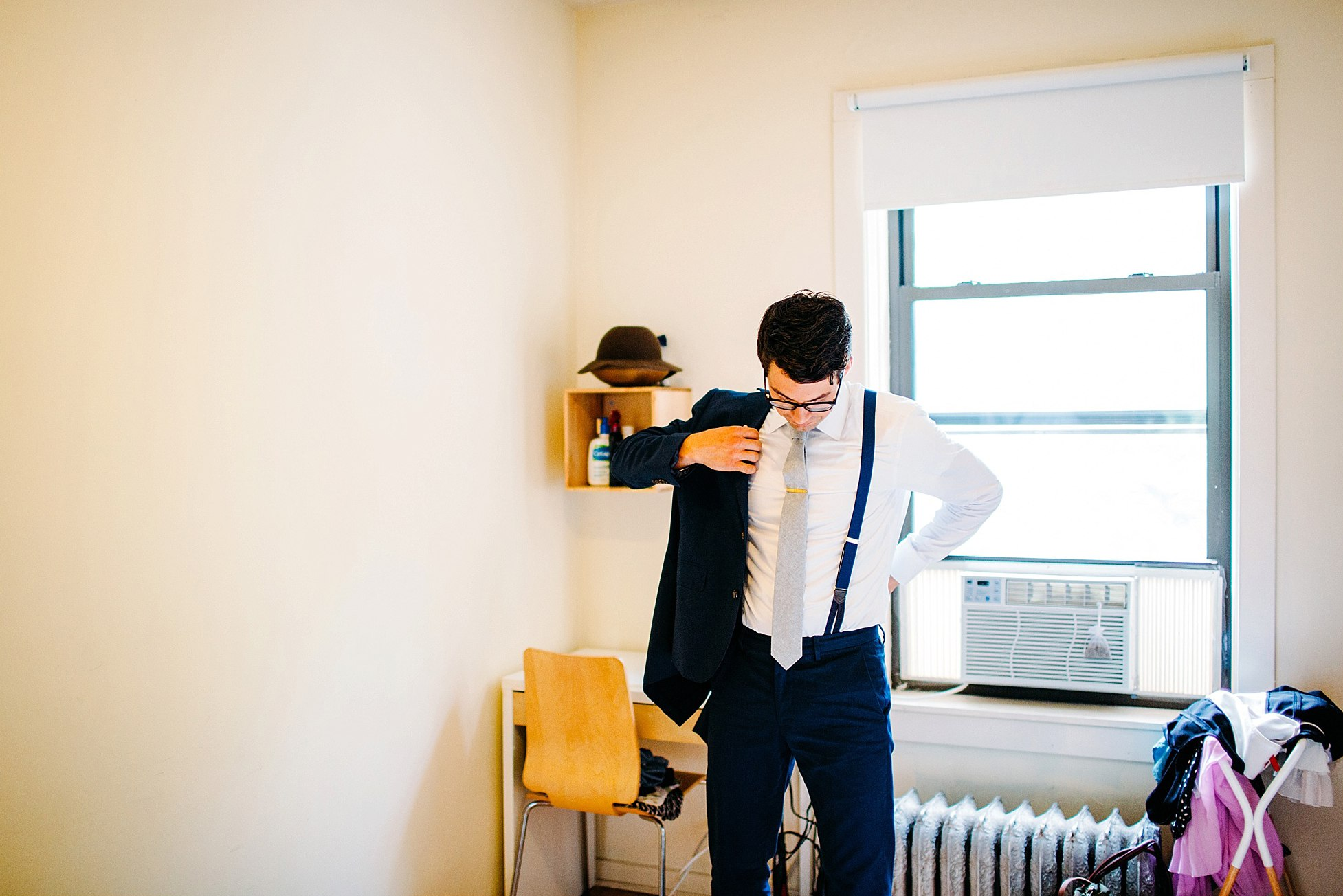Jacob Johnson getting dressed to marry Anjali pinto in greenhouse loft Chicago wedding