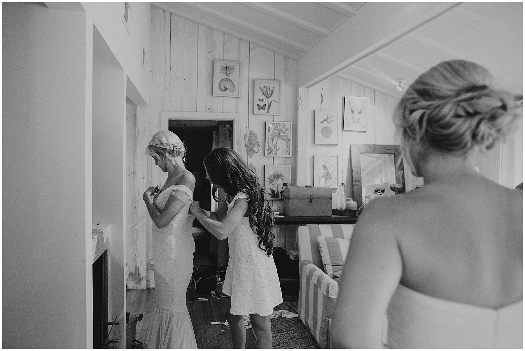 bride helping her maid of honor into dress