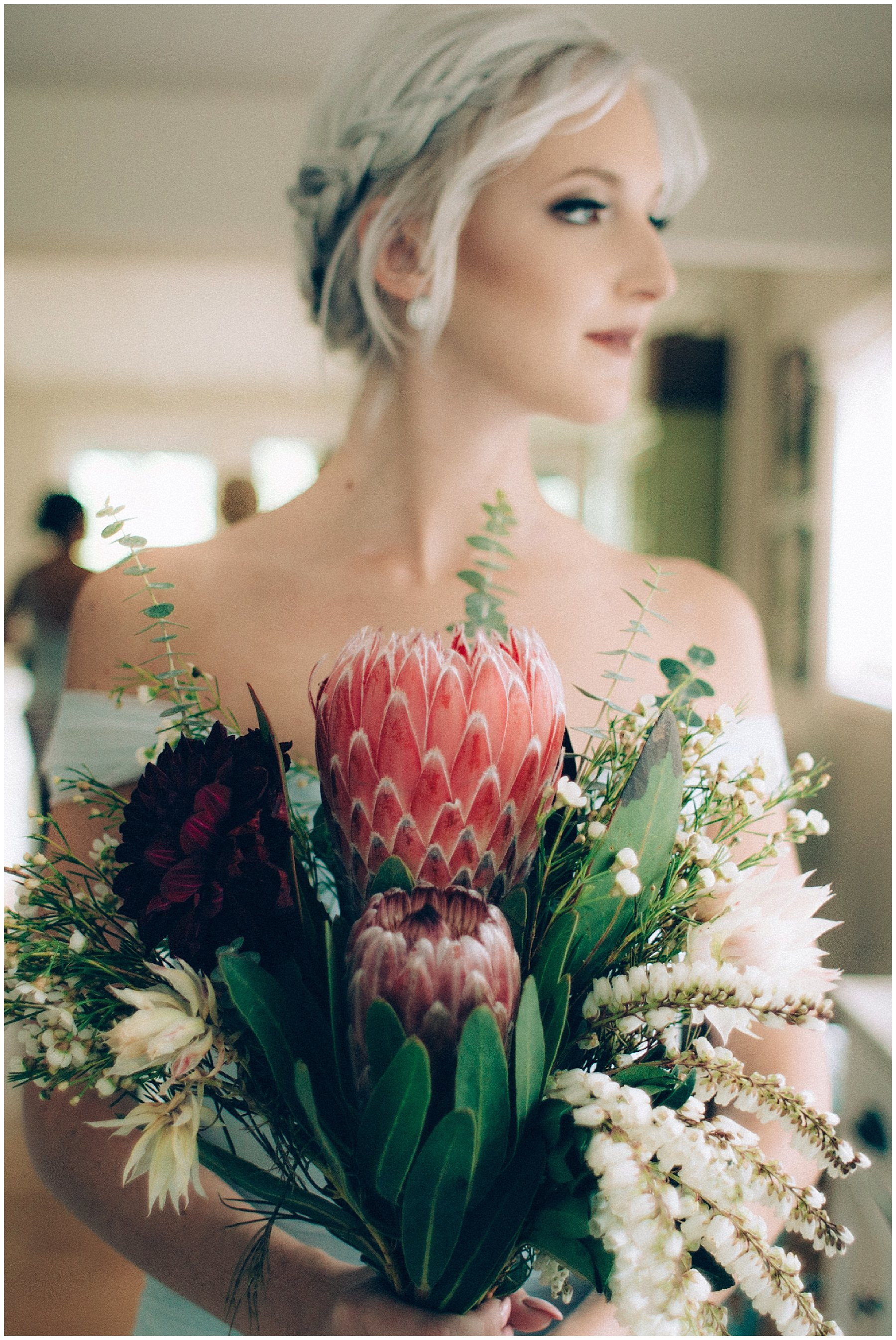 bridesmaid with grey hair holding protea bouquet in natural light