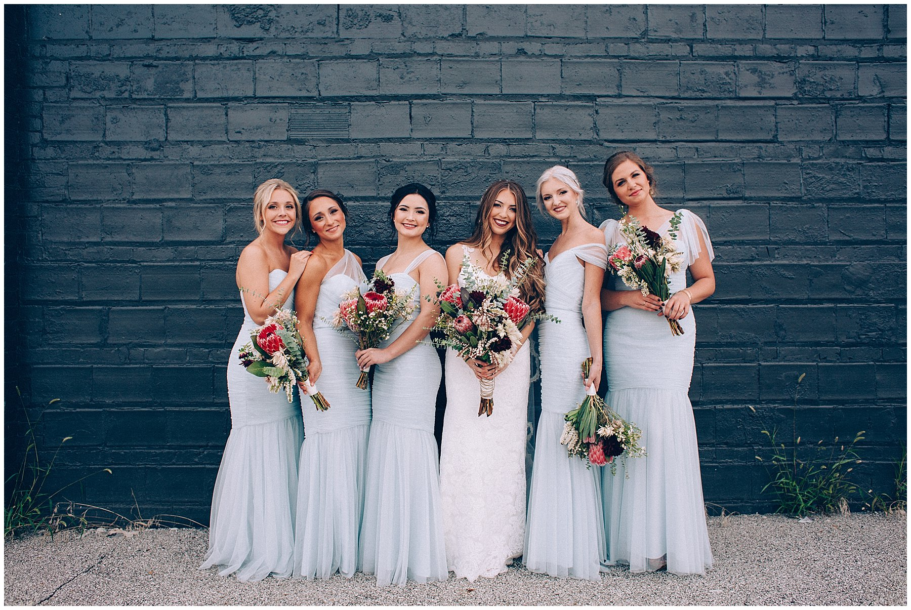 bridesmaids in pale blue dresses with bright protea bouquets