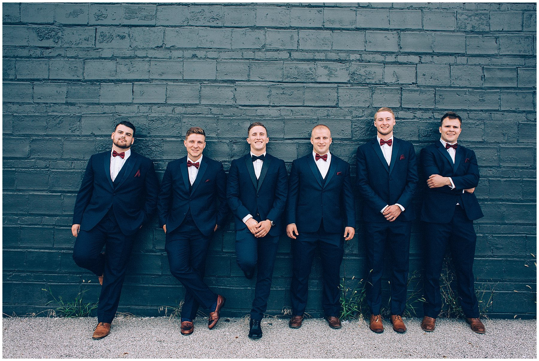 grooms in dark blue tux with Burgundy bowties