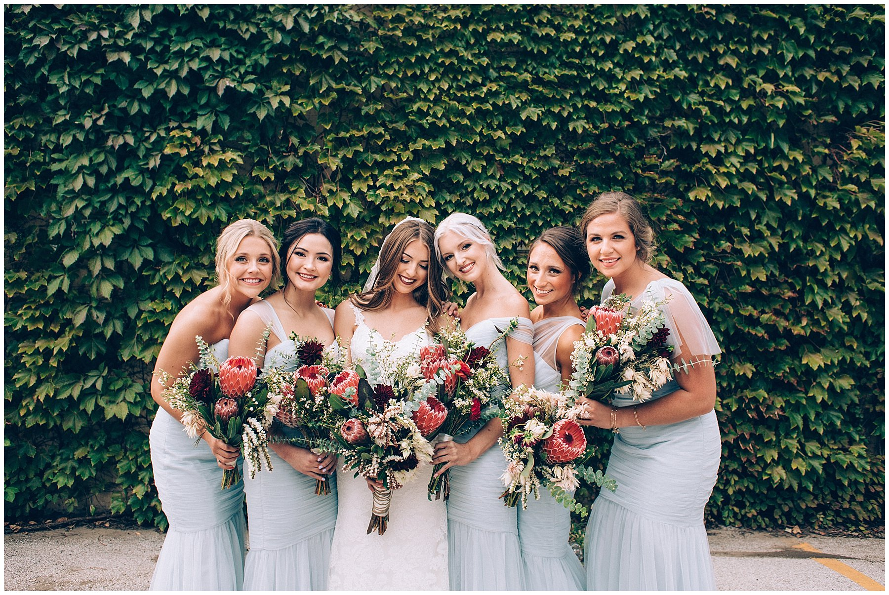 bridesmaids in front of ivy wall with protea bouquets