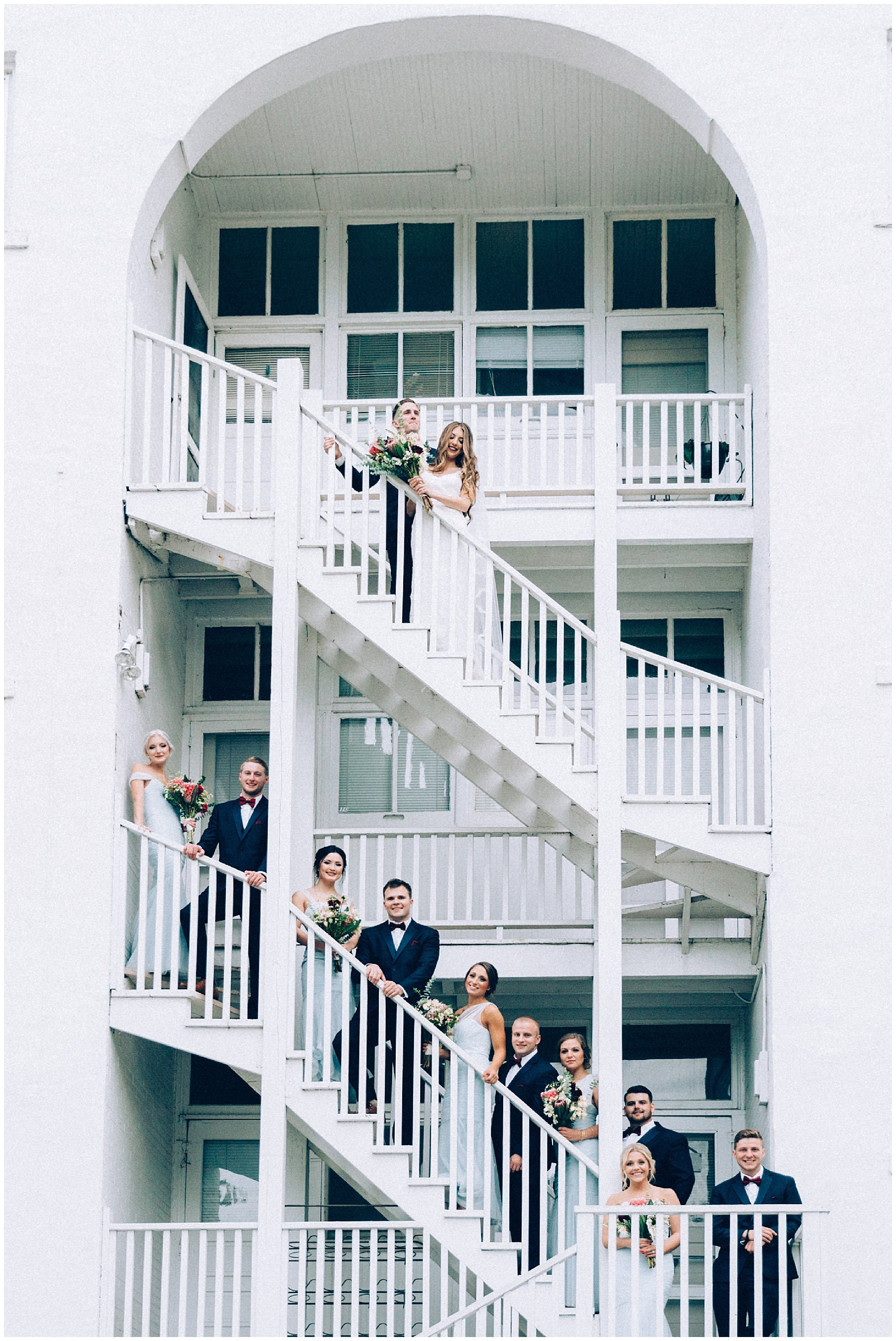 bridal party arranged in art gallery staircase Des Moines