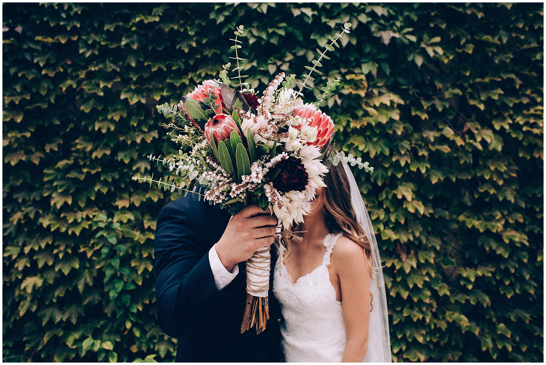 groom hiding behind protea bridal bouquet sneaking a kiss