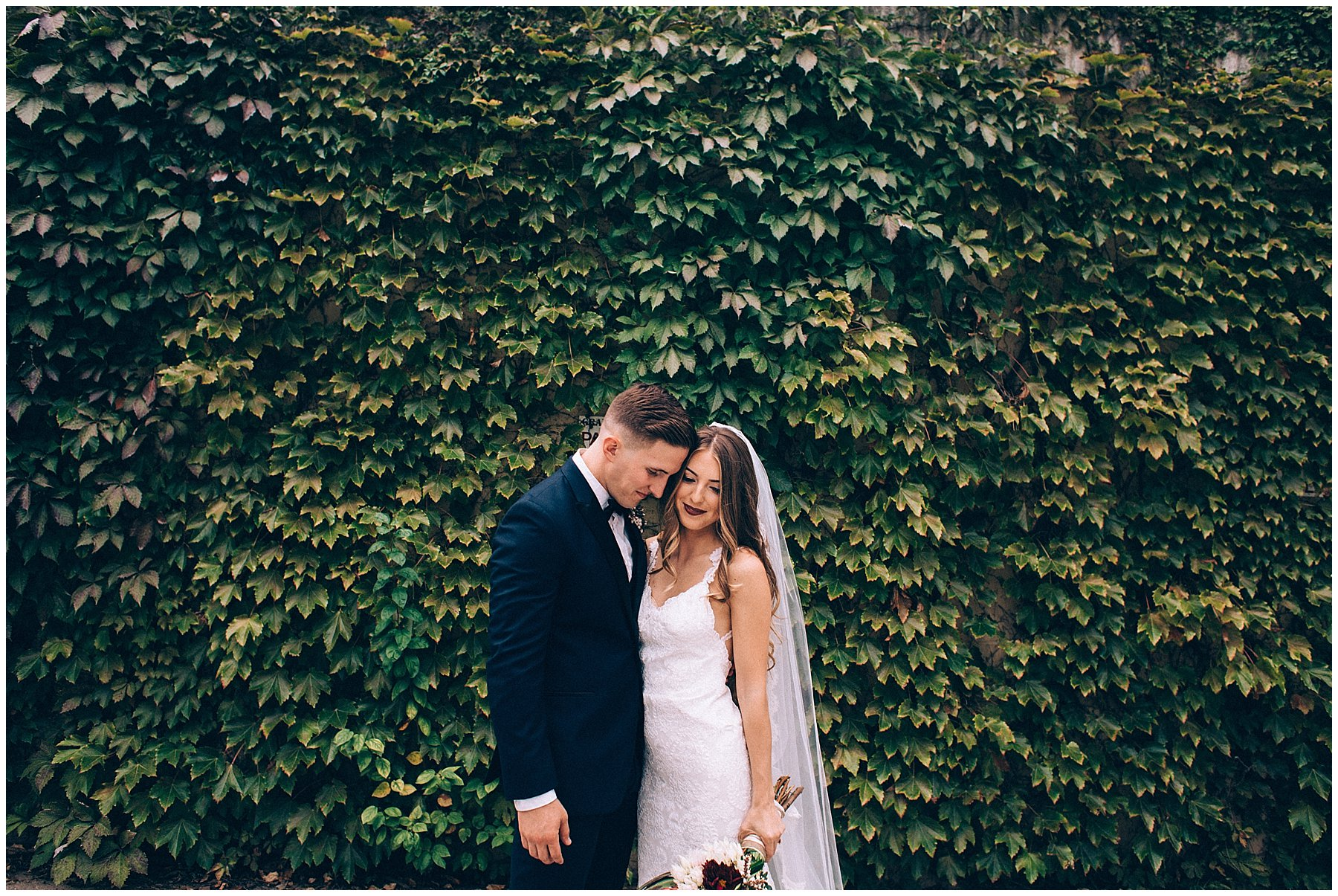 bride and groom in front of ivy wall for Des Moines wedding