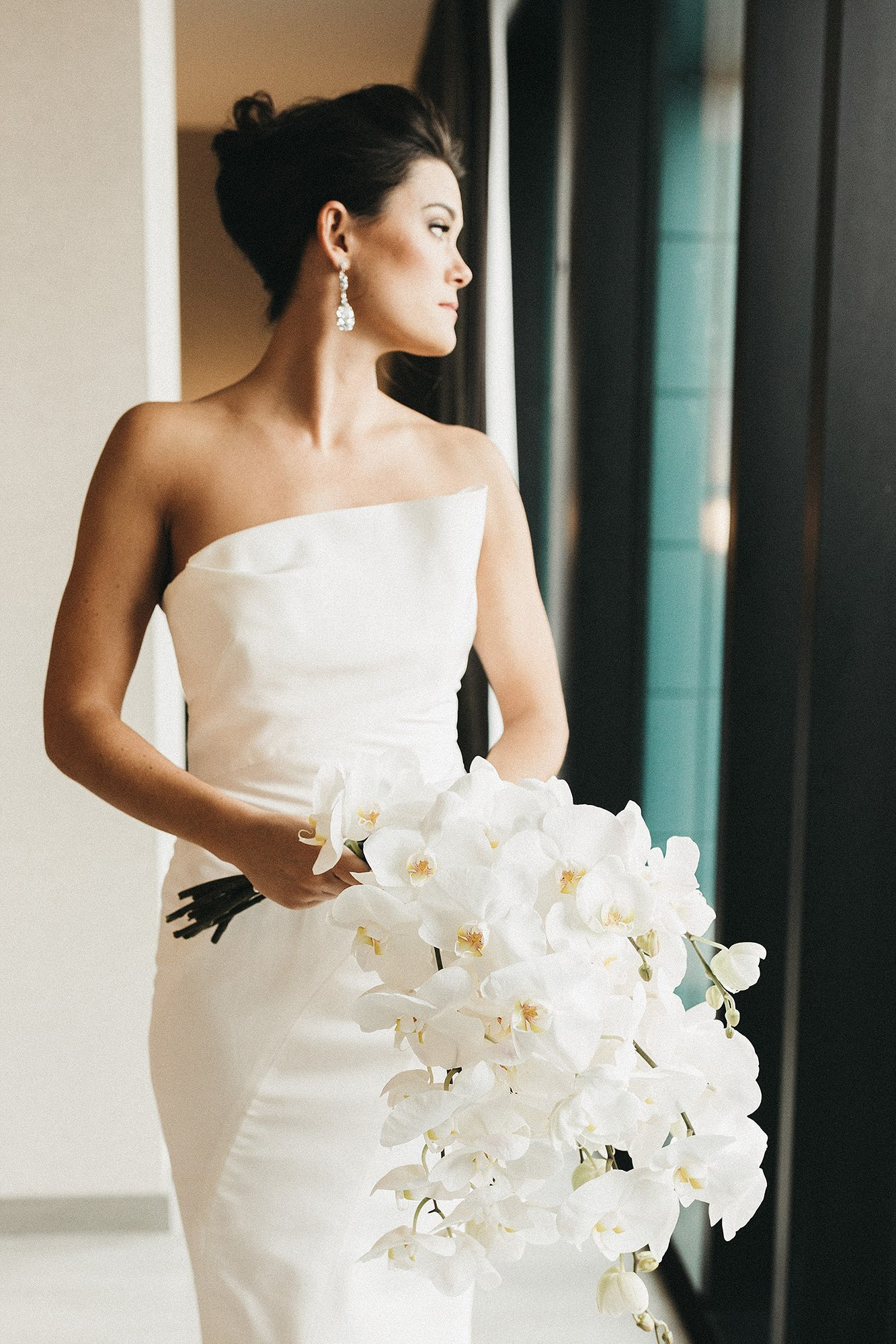 The bride in her asymmetrical gown by J. Mendel and her asymmetrical orchid bouquet