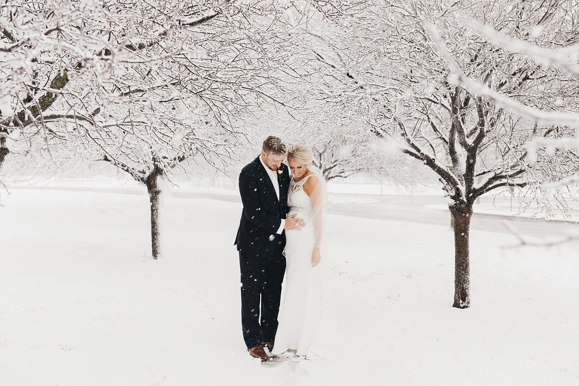 snowy winter wedding with pregnant bride in vintage gown