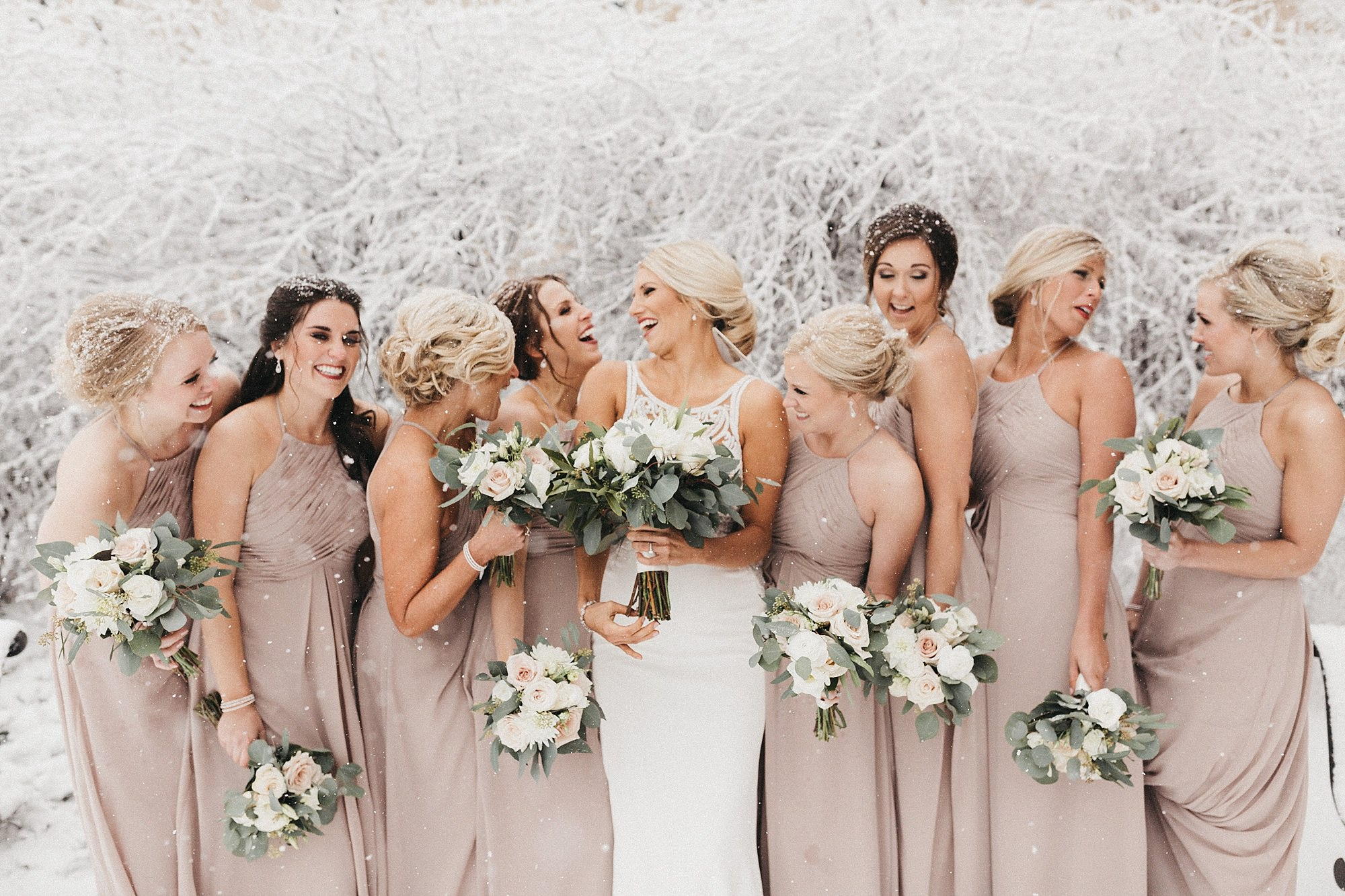 bridal party in the snow at winter Maytag center wedding in newton Iowa