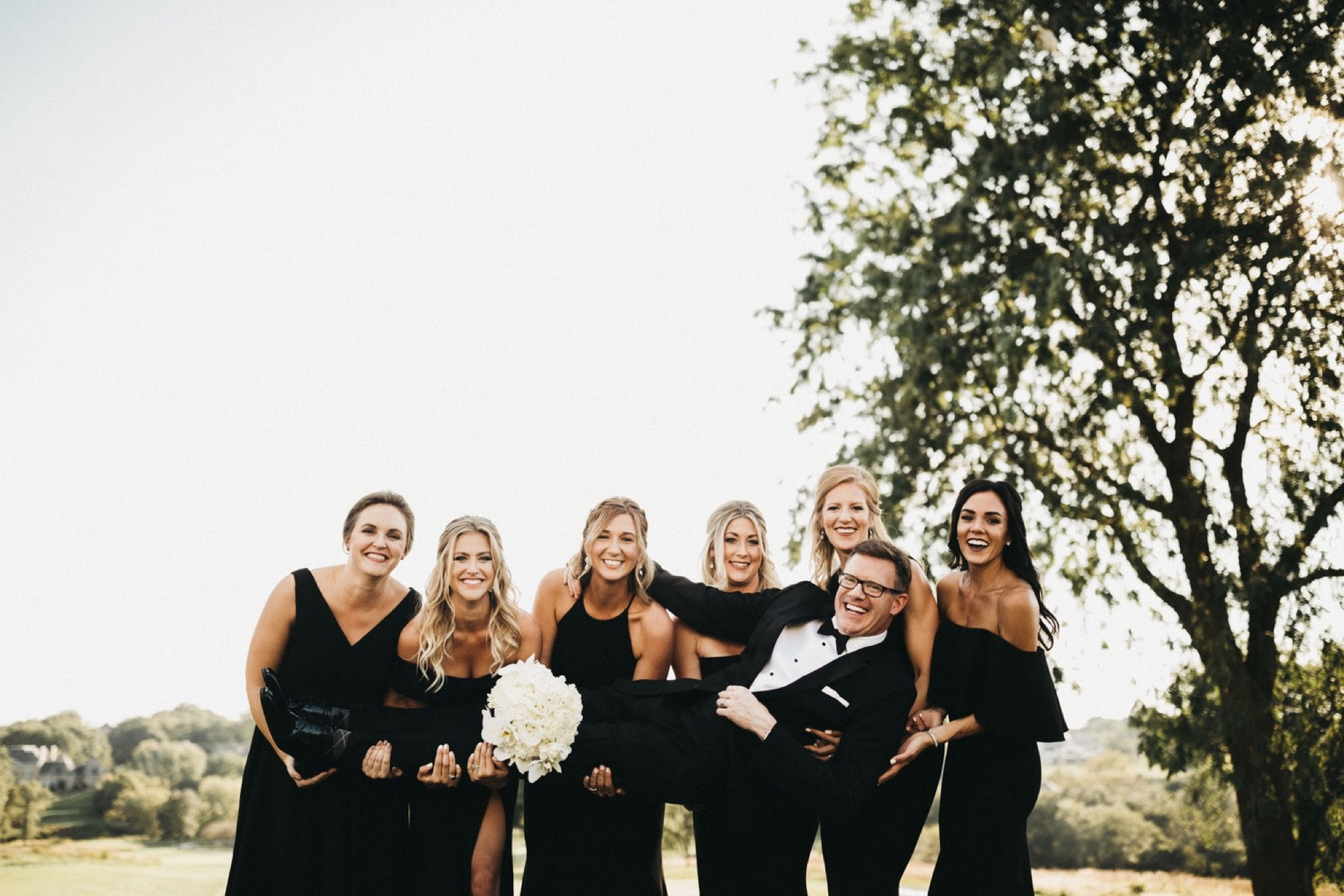 bridal party holds groom up at modern glen oaks wedding in des moines