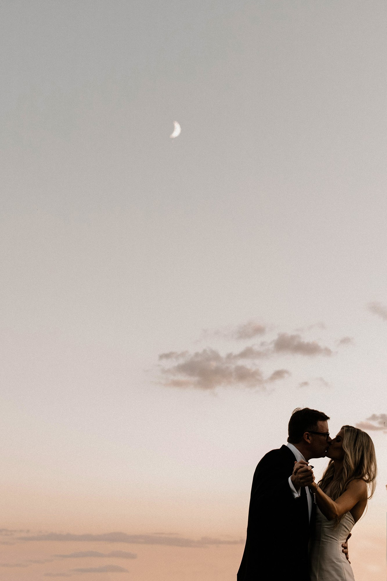 bride and groom embracing under a moonlight pink sky