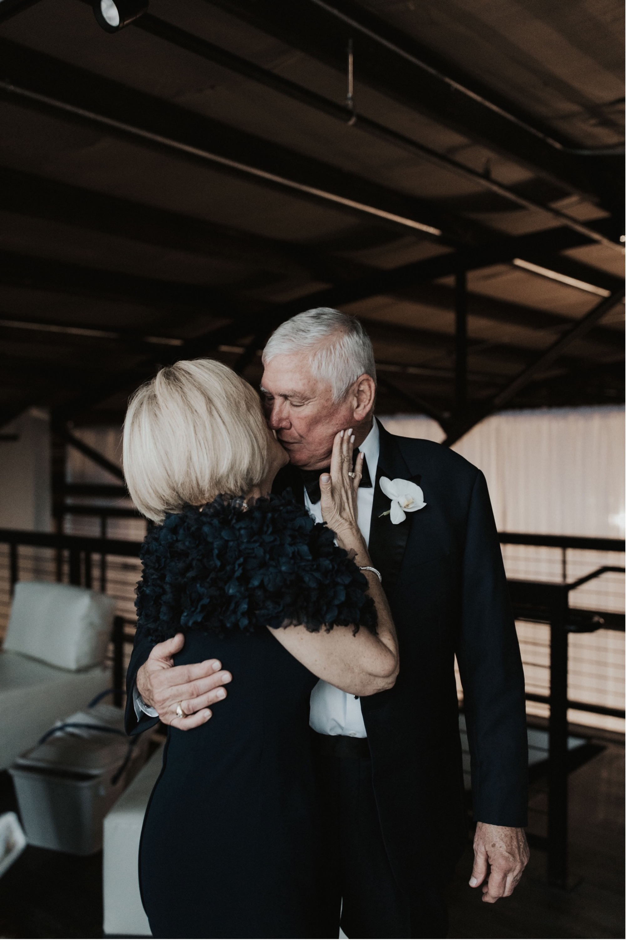 mother and father of the bride kissing during curate wedding in Des Moines
