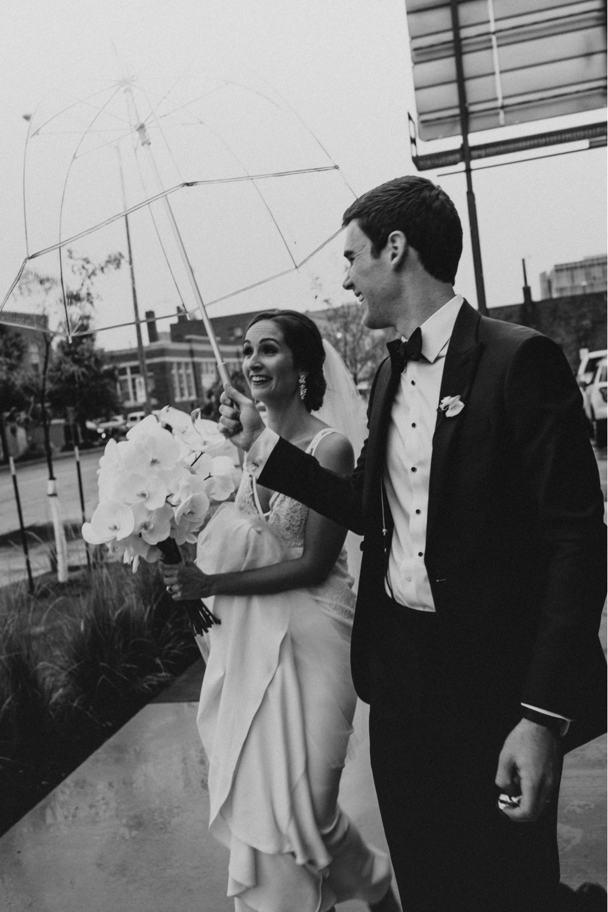 bride and groom caught in rain after curate Des Moines wedding