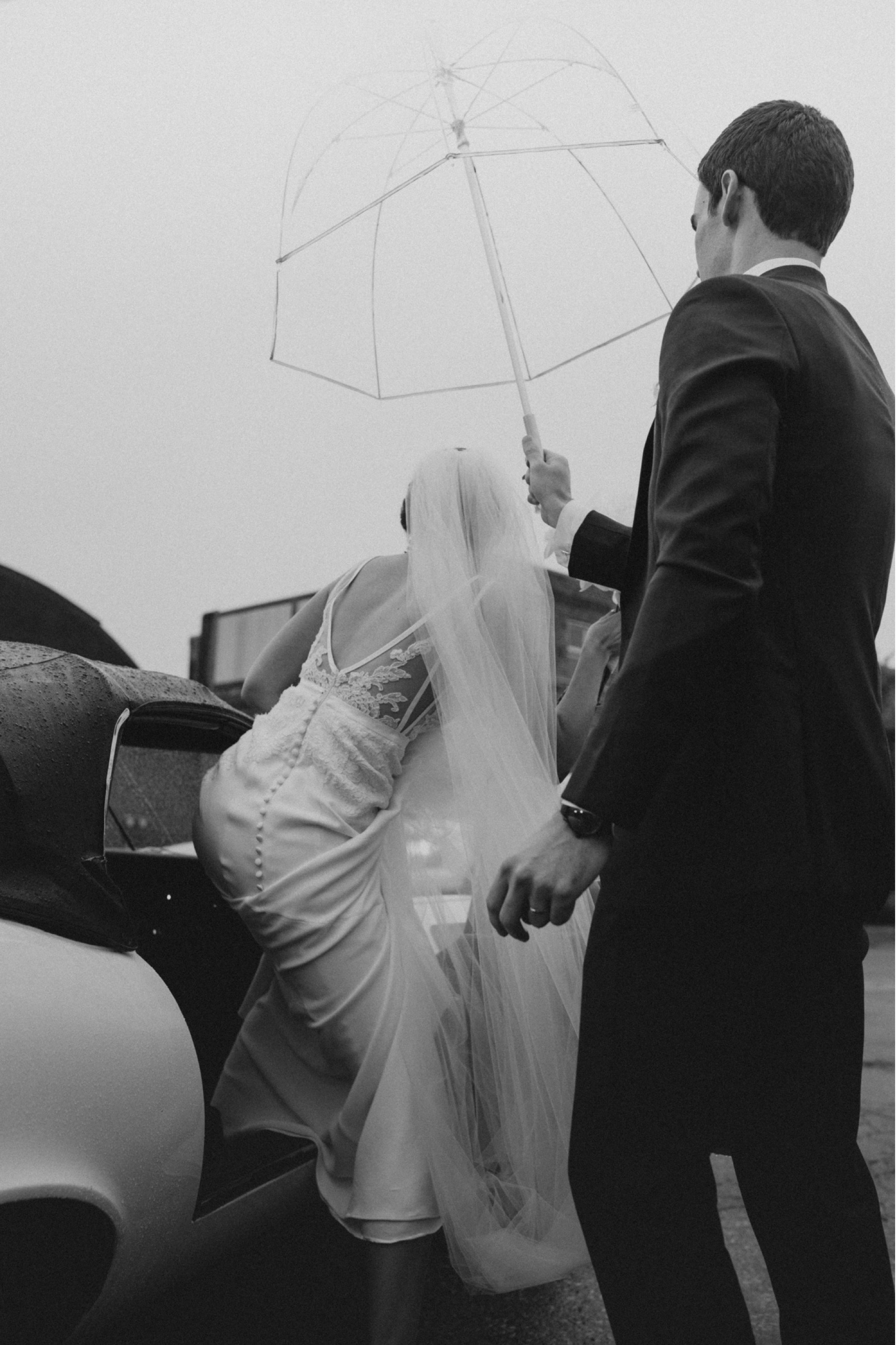 anne barge bride in rain getting into vintage jaguar after curate Des Moines wedding