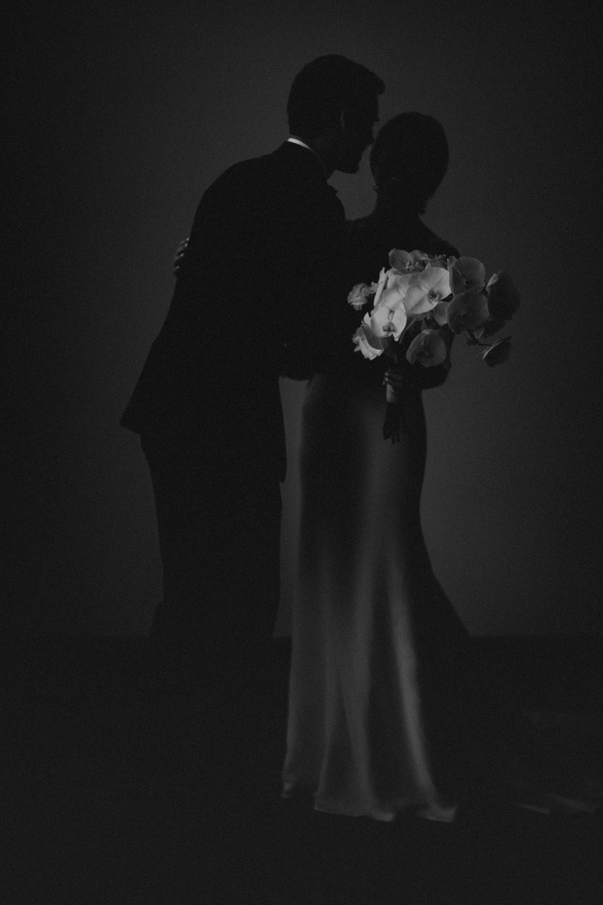 romantic silhouette of couple with orchid bouquet at tea room wedding in Des Moines