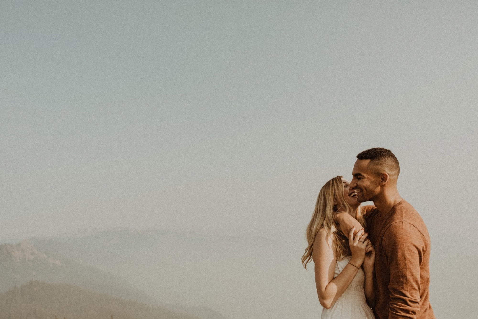 bride and groom kissing and laughing at hurricane ridge during engagement shoot