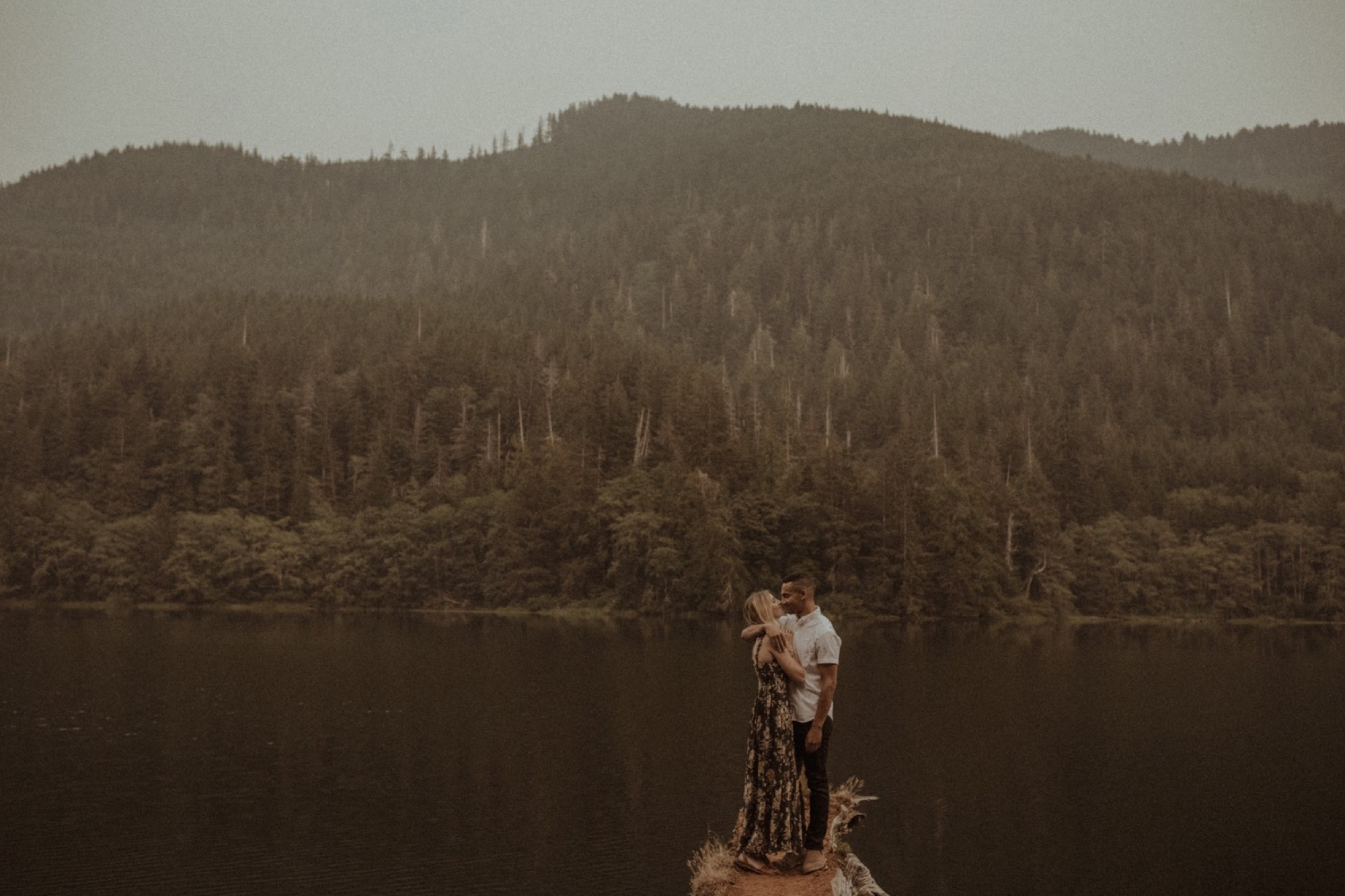 couple embracing on lake in olympic national park during engagement shoot