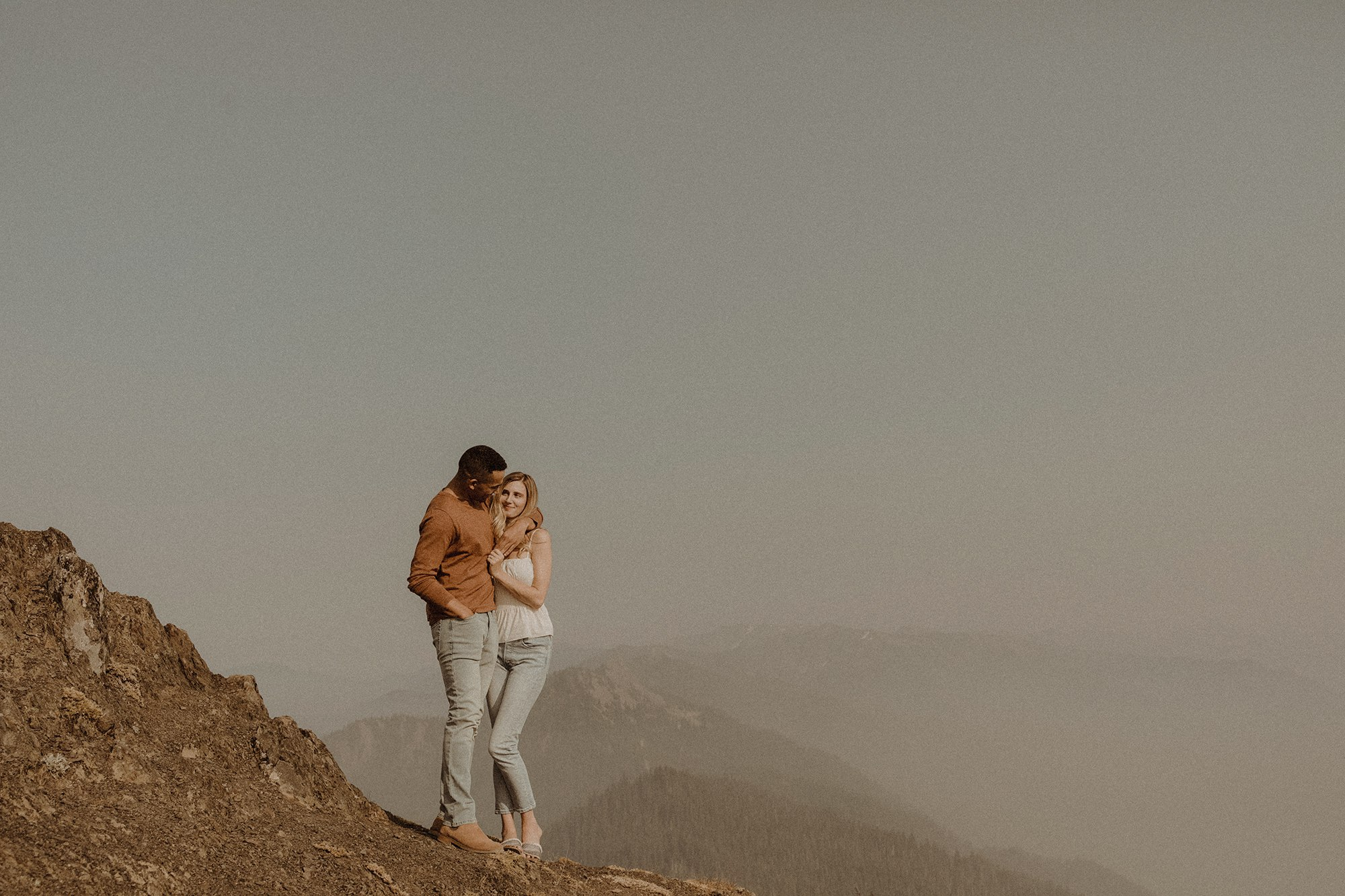 couple embracing on smokey hurricane ridge during engagement shoot