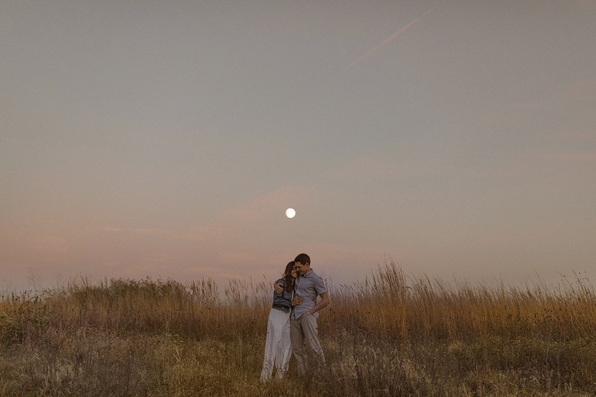 couple embracing under an epic pink moonrise
