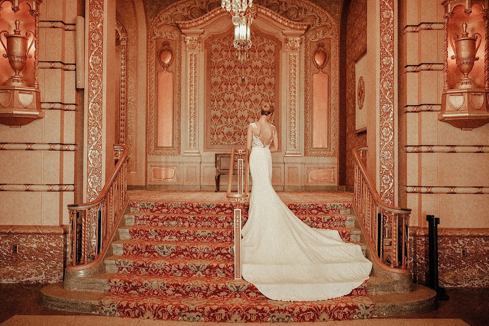 old Hollywood pose bride in pronovias wedding gown in golden historic wes Anderson paramount theater