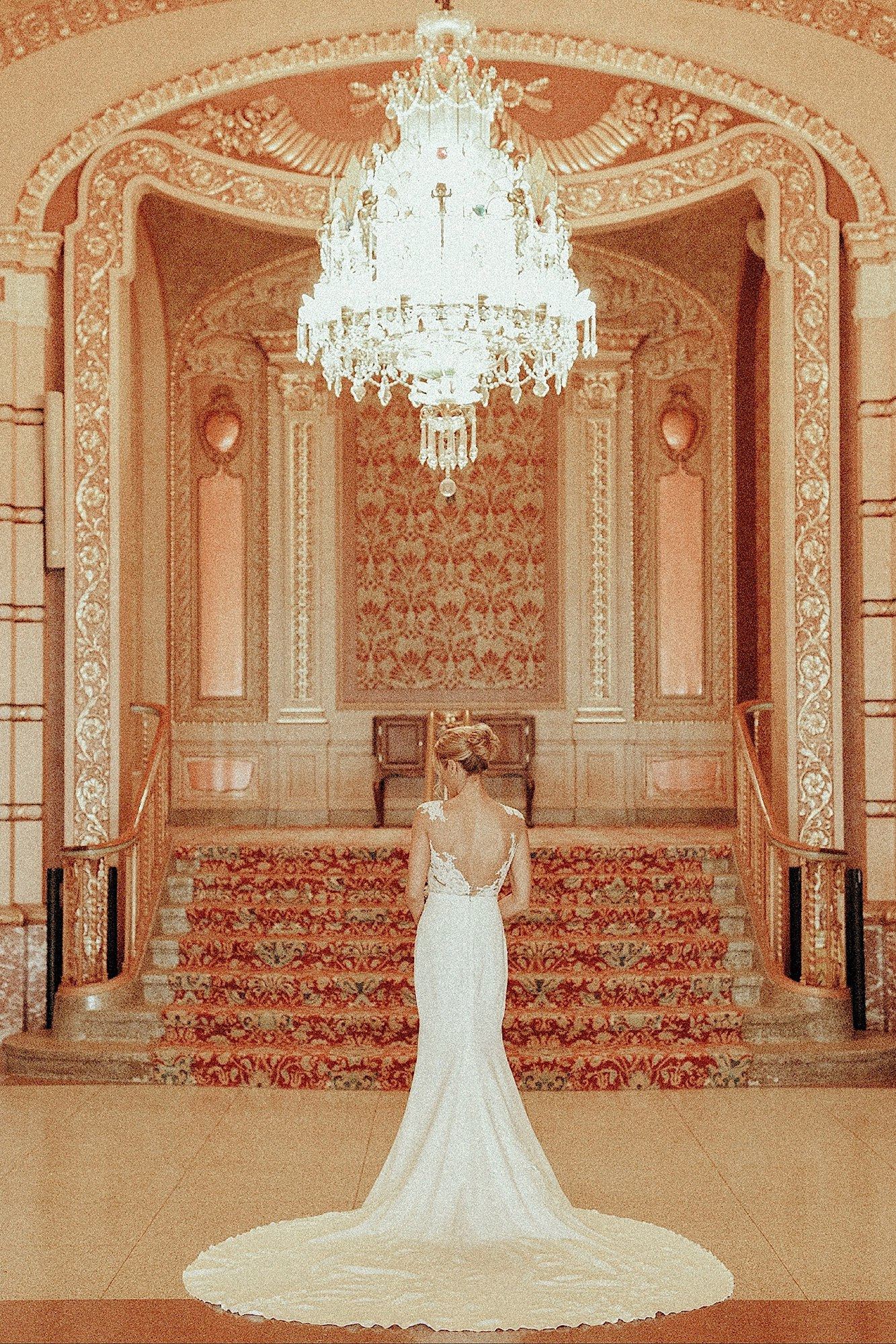pronovias bride standing in pronovias gown in golden historic paramount theater