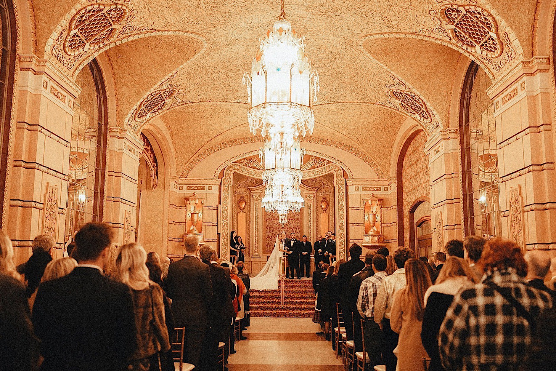 bride and groom saying vows in golden historic paramount theatre winter wedding
