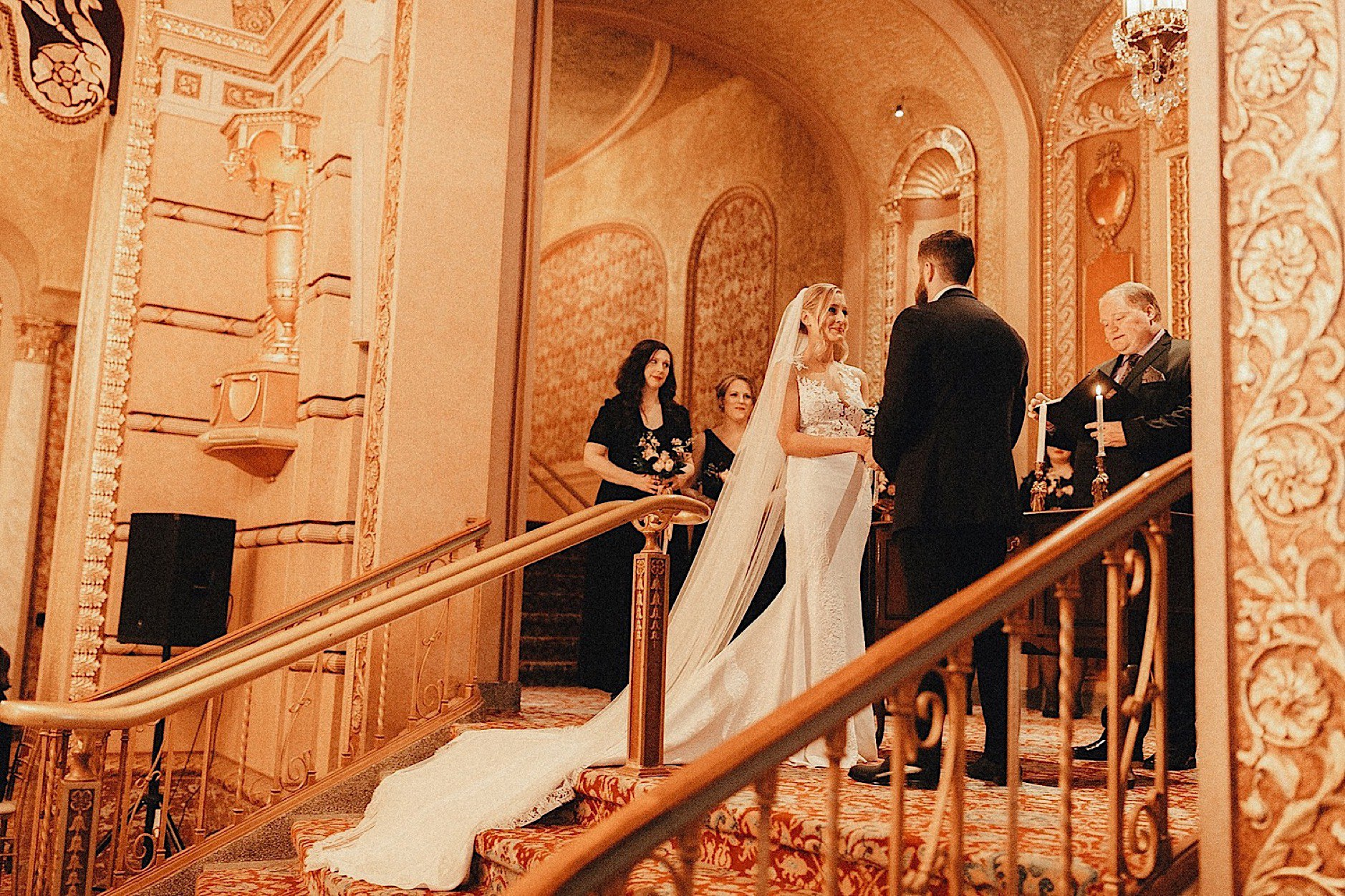 pronovias bride and groom saying vows in golden historic paramount theatre winter wedding