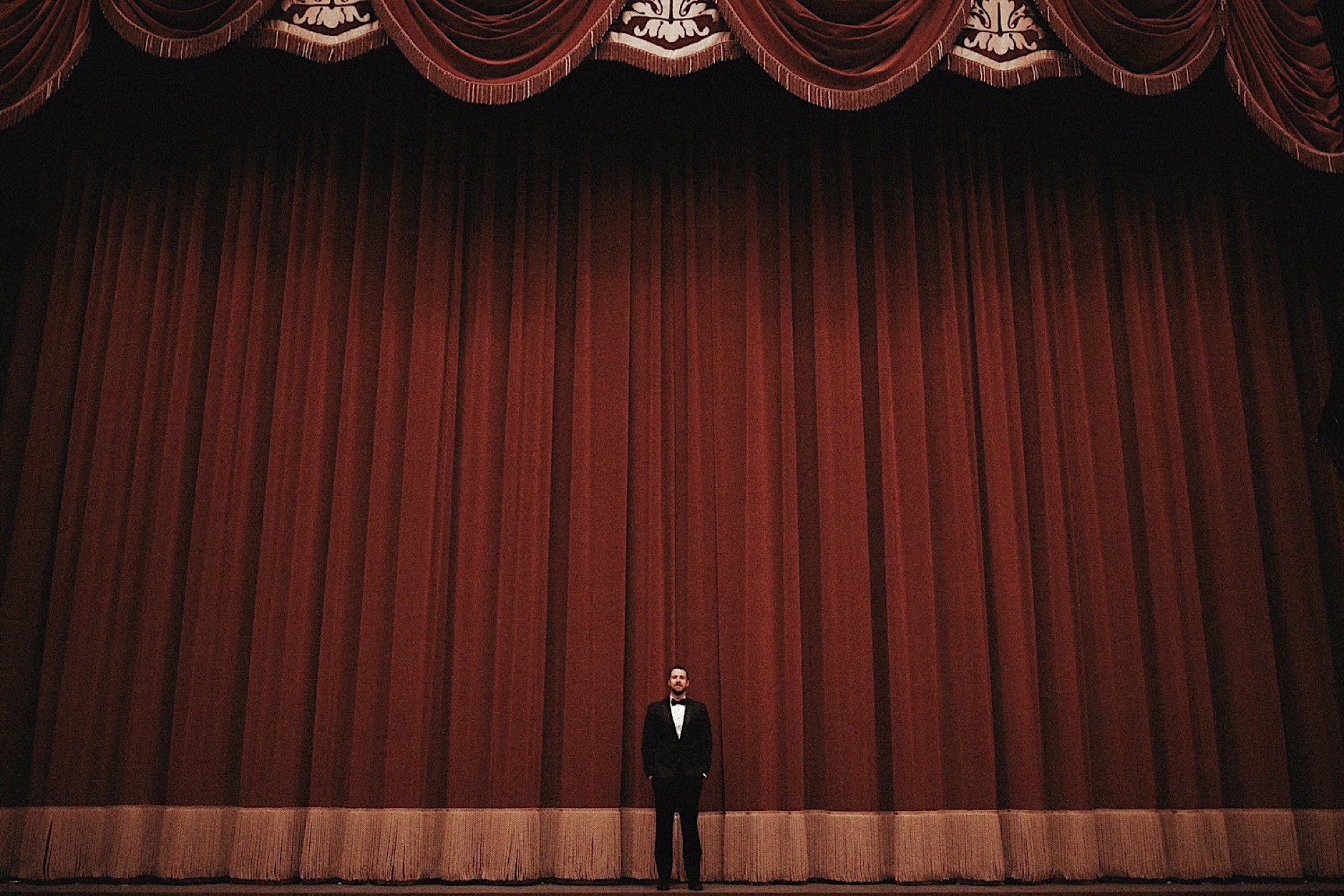 groom in front of red curtain at historic paramount theatre wedding