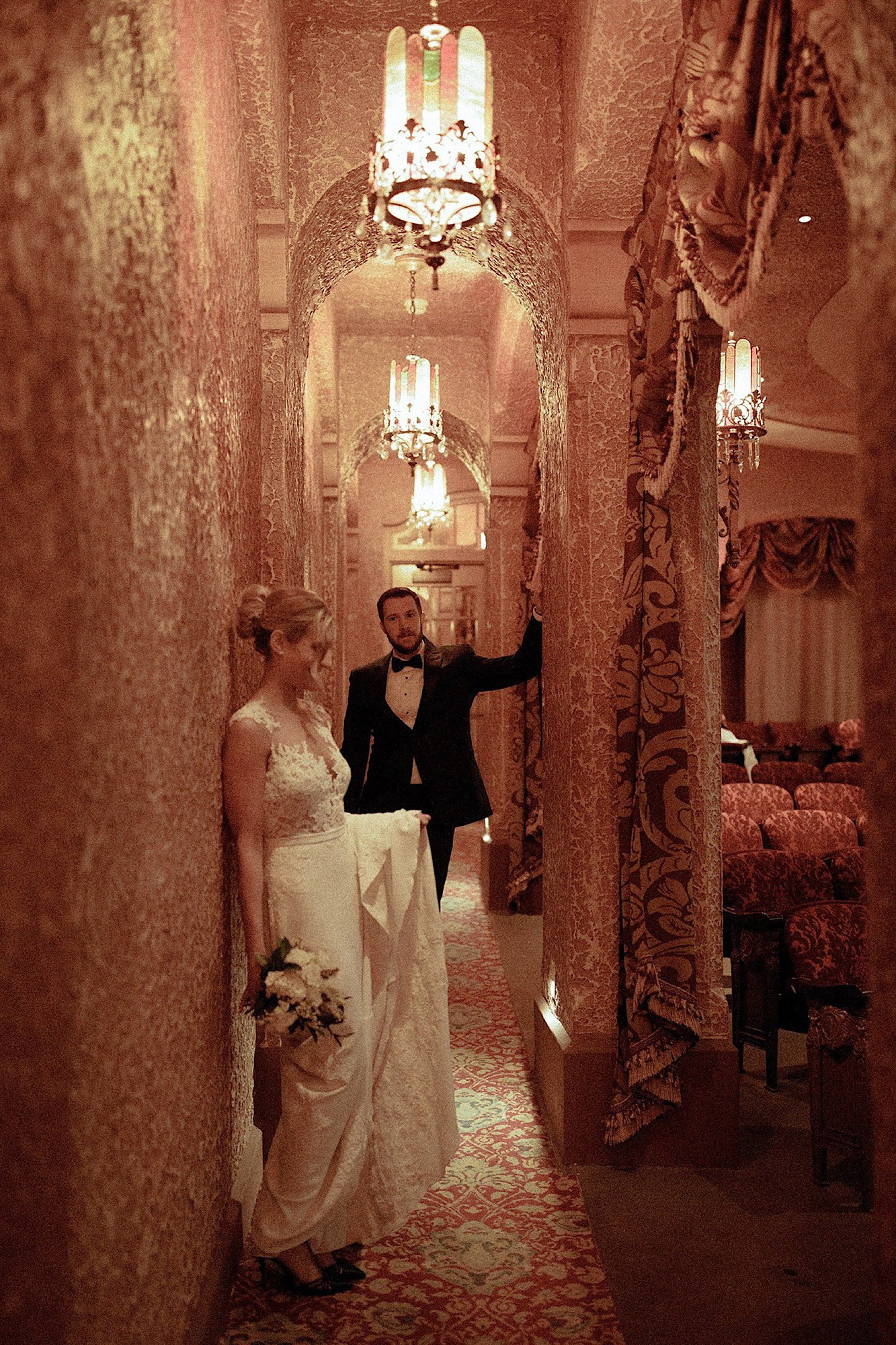bride and groom posed in golden hallway at historic paramount theatre wedding