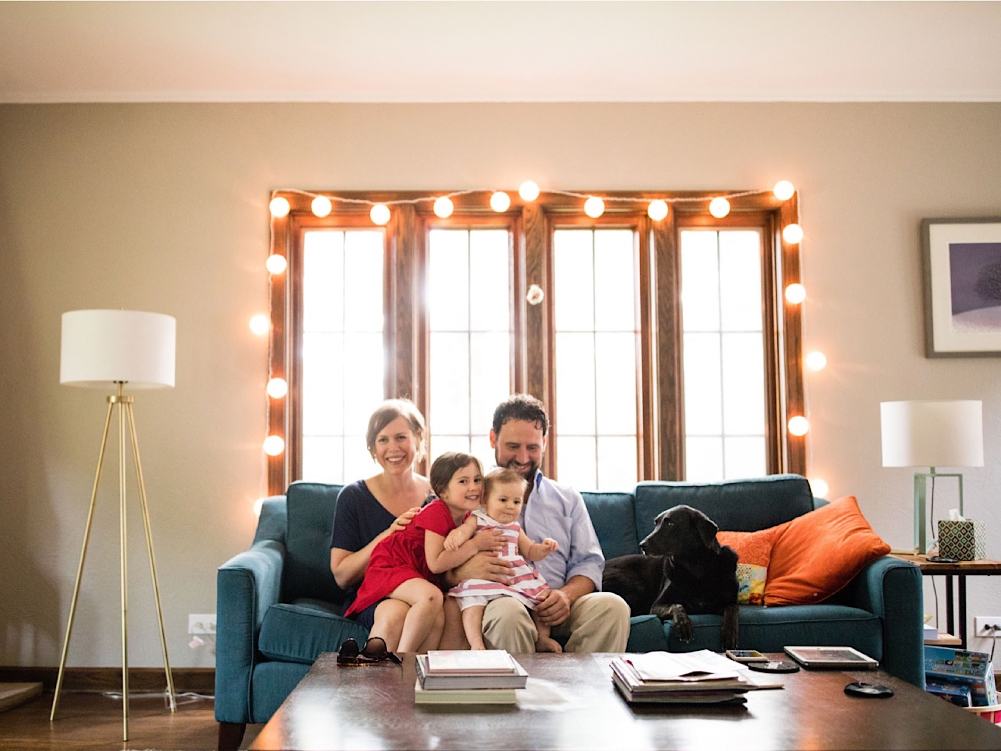 family smiling in living room during family photo session in Des Moines Iowa