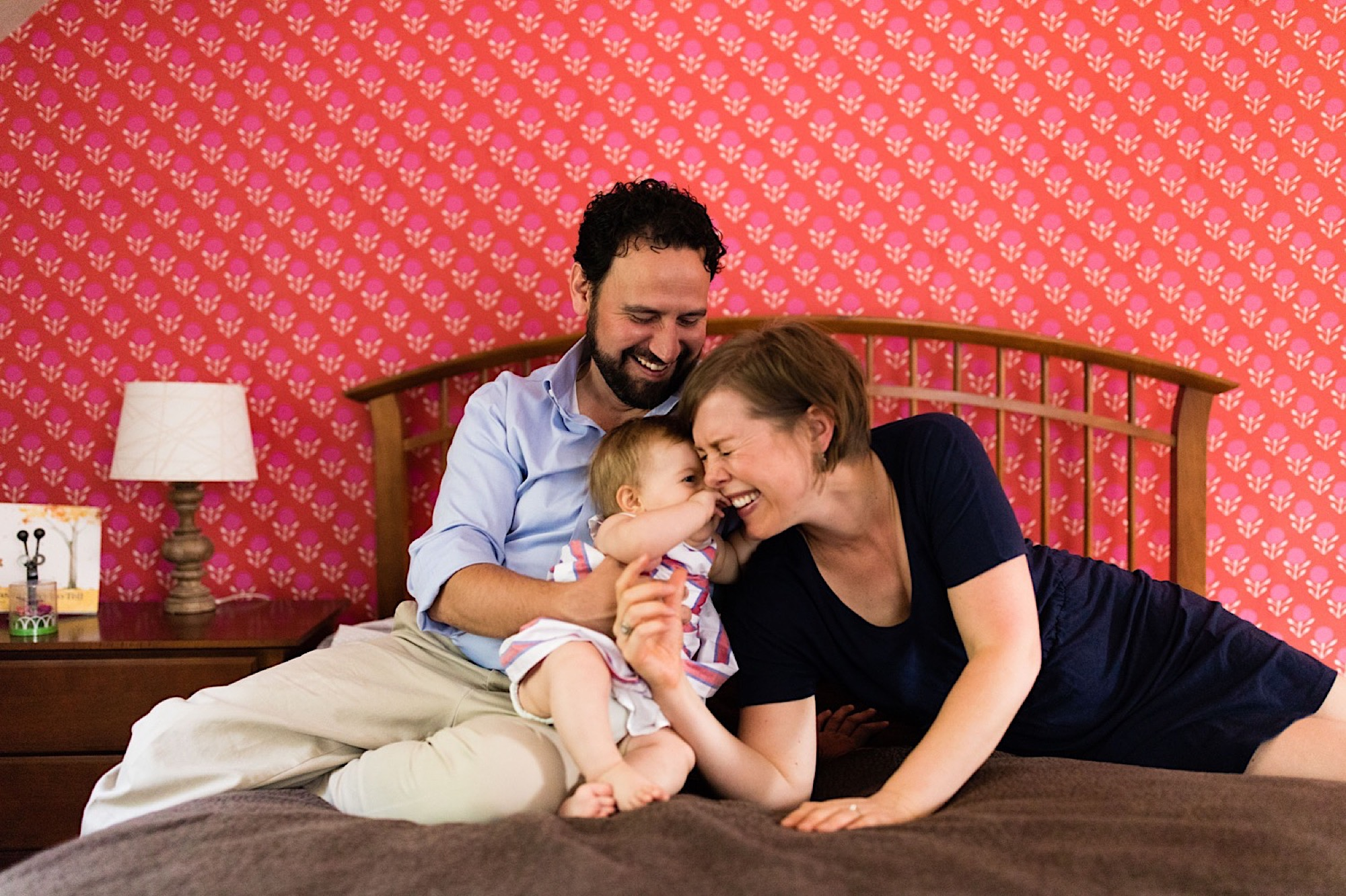 family snuggling on bed smiling at new baby