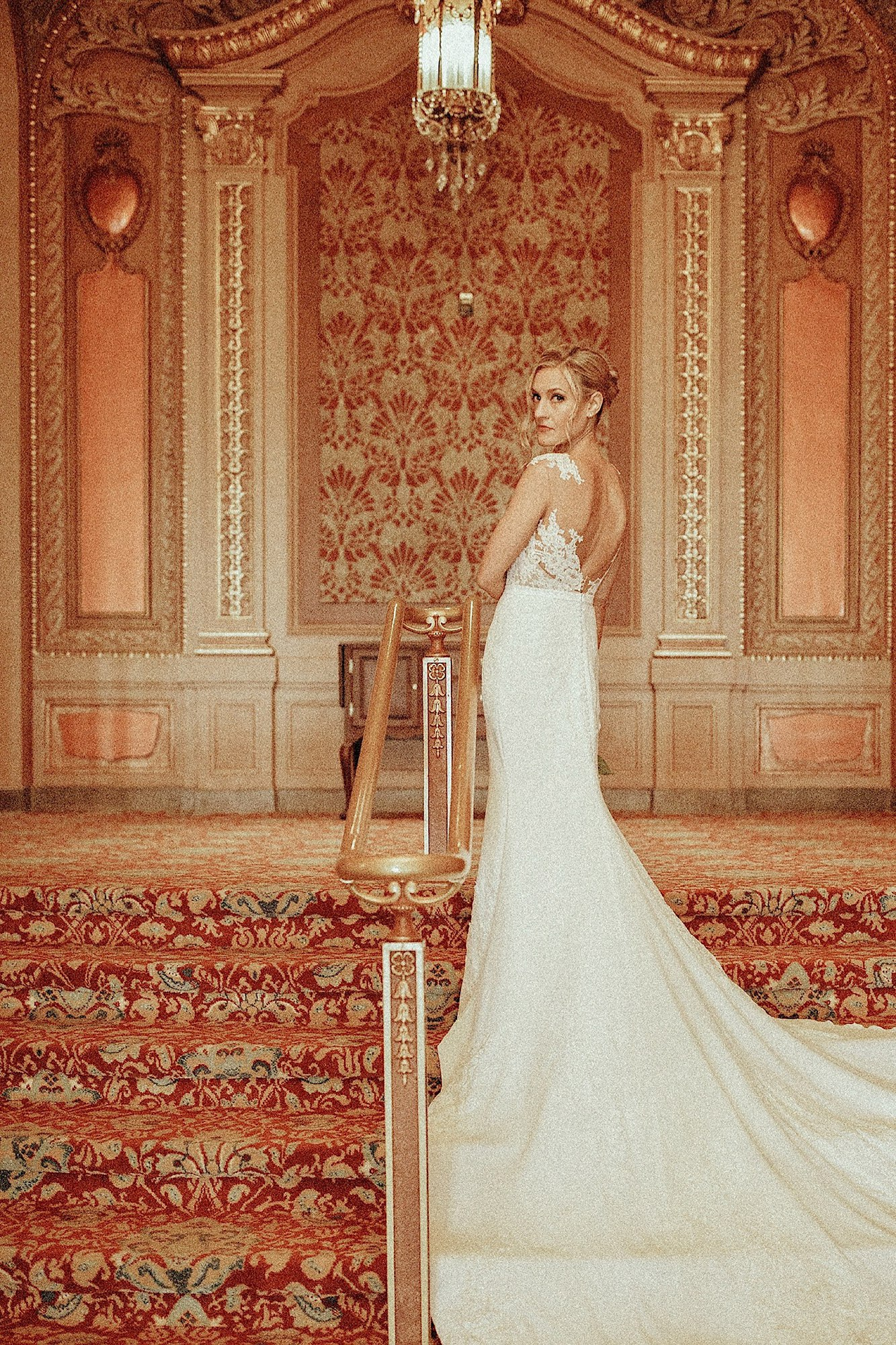 wes Anderson wedding bride standing in pronovias gown in golden historic paramount theater
