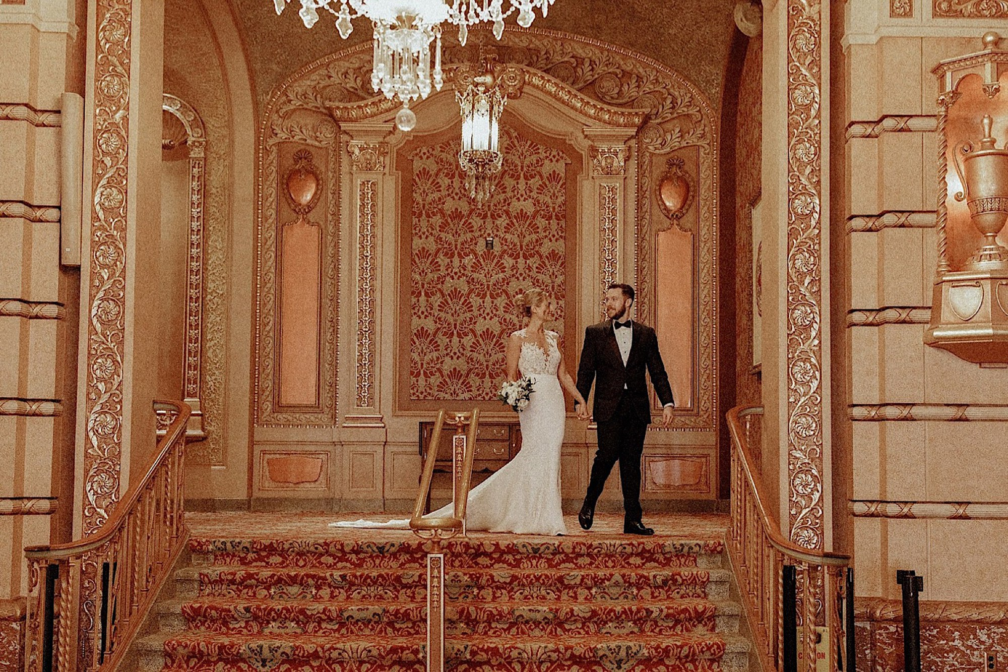 wes Anderson wedding bride and groom in golden historic paramount theater