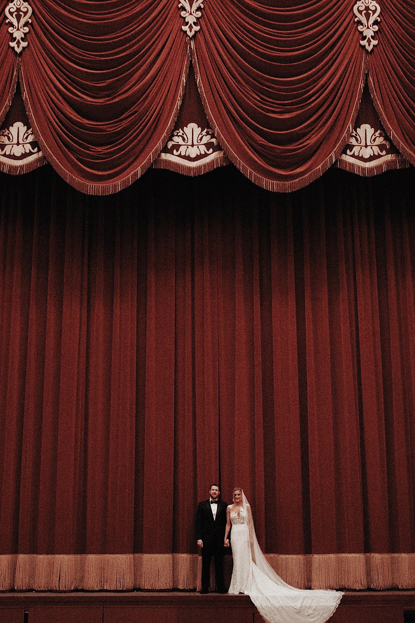 wes Anderson wedding bride and groom standing dramatically in historic theater