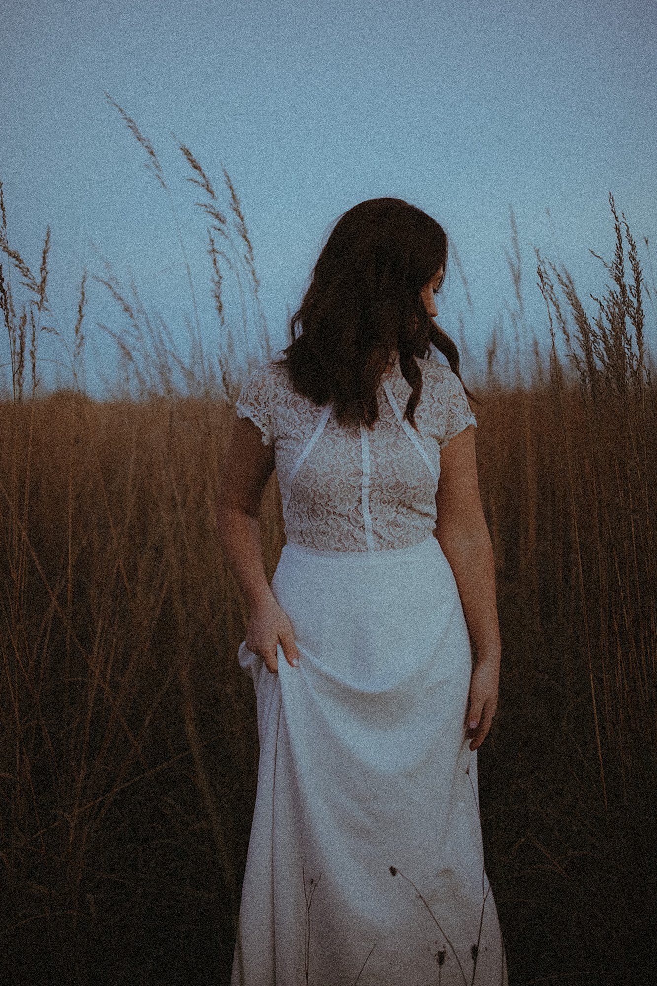 bride in field of wheat at dusk