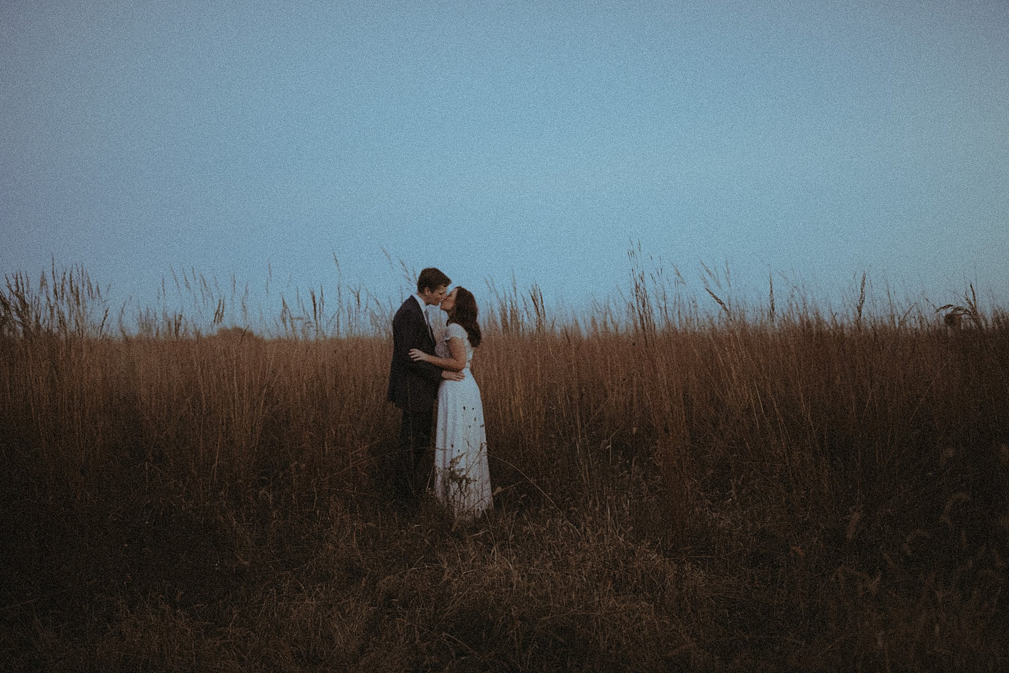 bride and groom kissing at dusk in field of grass