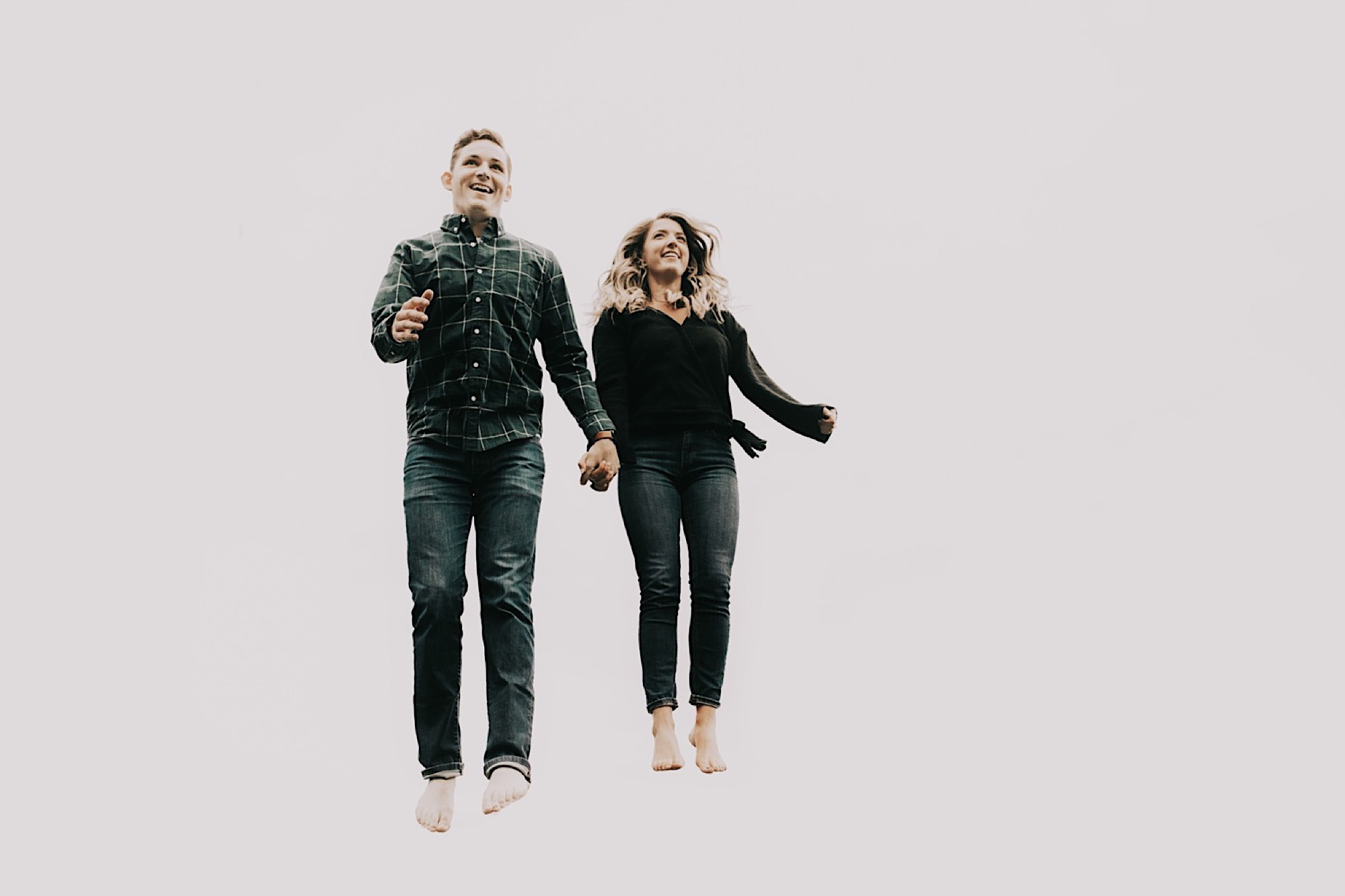 couple jumping through air during Des Moines engagement shoot