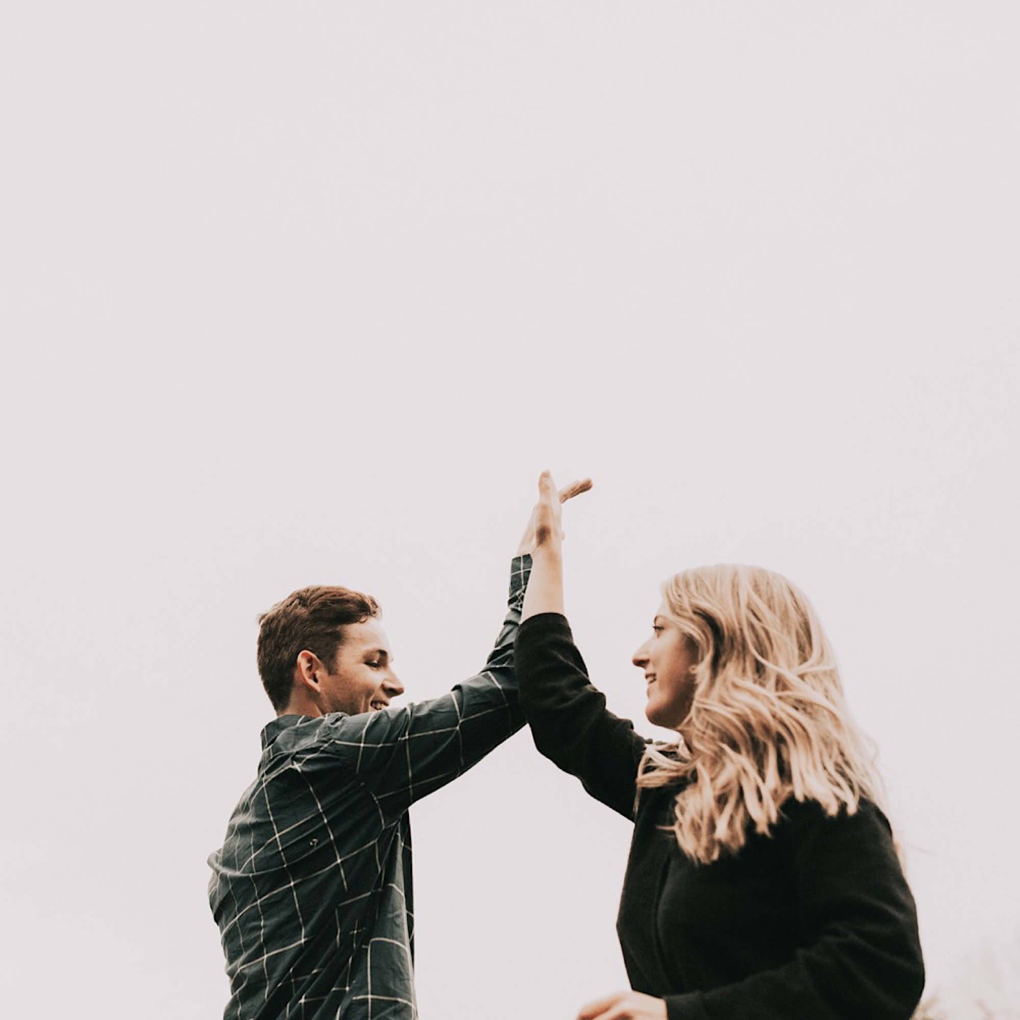 couple high-fiving during at-home engagement shoot