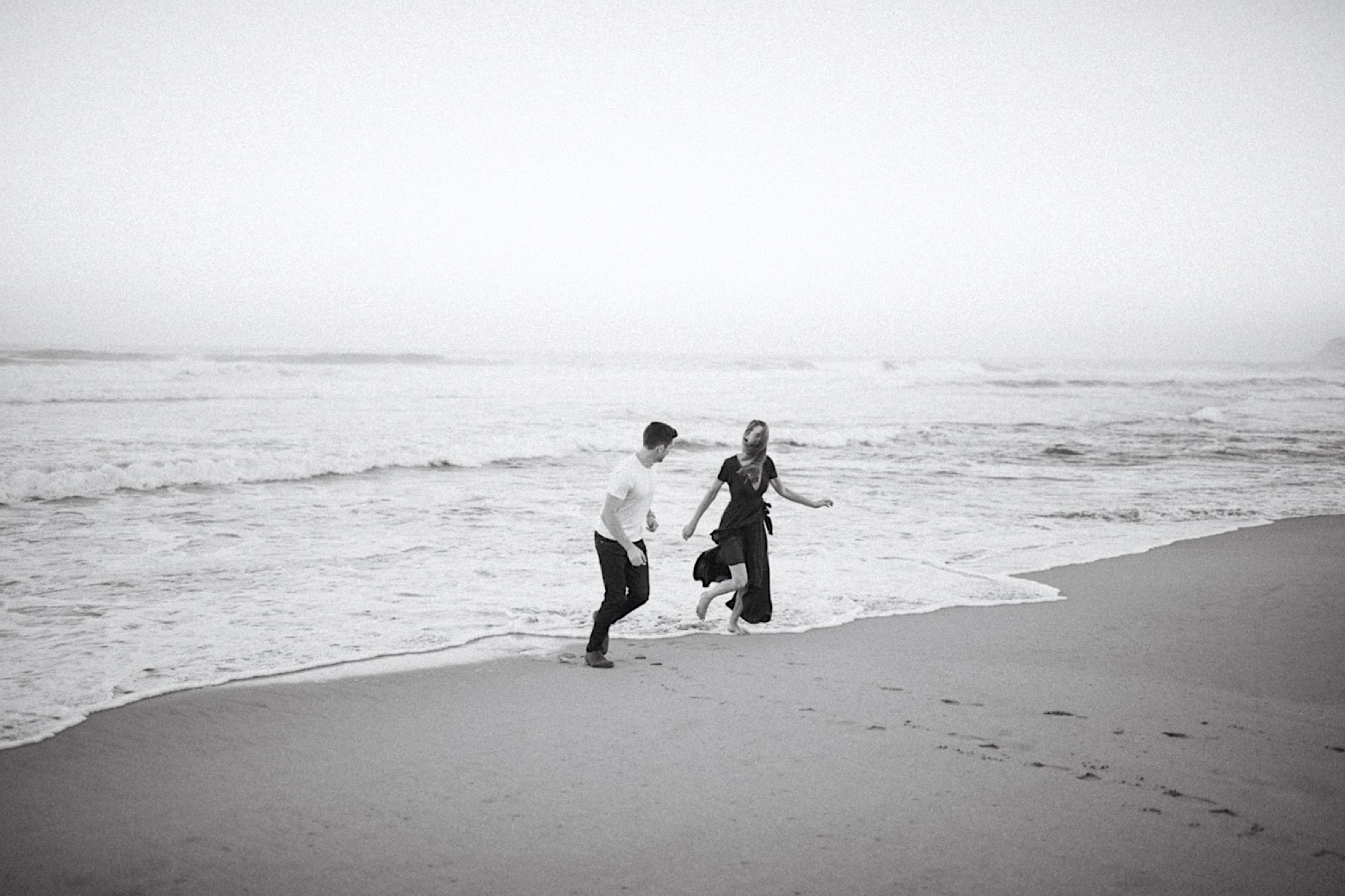 couple laughing on the beach at half moon bay during engagement session